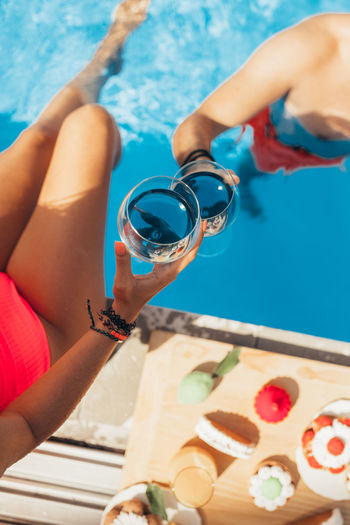 High angle view of hands holding ice cream in swimming pool