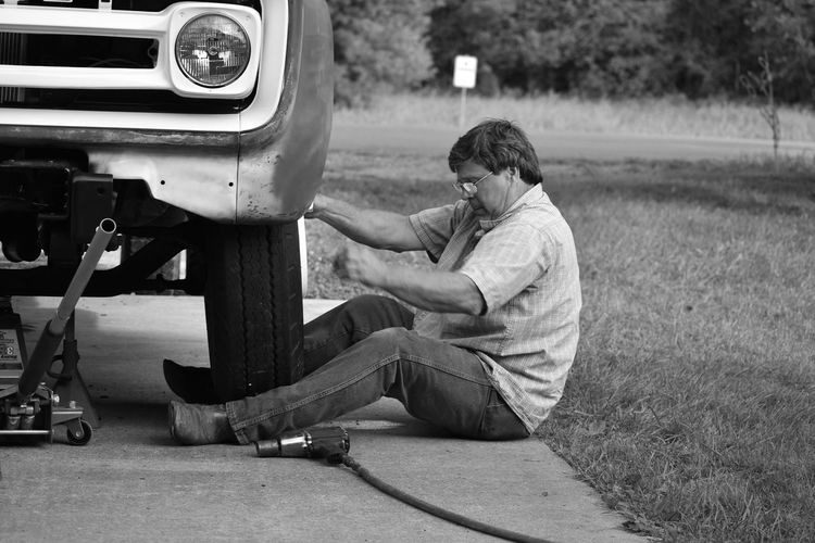 Side view of man changing tire