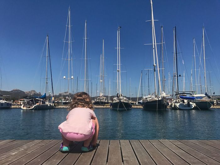 Rear view of baby girl crouching on pier at harbor with boats in background against clear sky