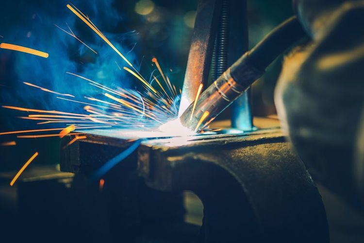 Machine welding metal at workshop
