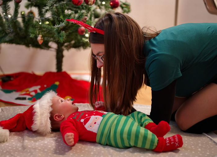 Mother playing with lovely baby near christmas tree