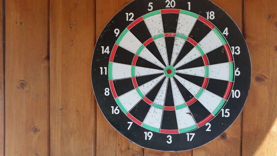 Close-Up Of Dartboard Mounted On Wooden Wall