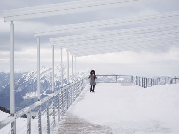 Snow Tourism Mountains Full Length Winter Railing Day Cloud - Sky One Person Outdoors Snow Cold Temperature Sky Real People Walking Lifestyles Architecture Shades Of Winter