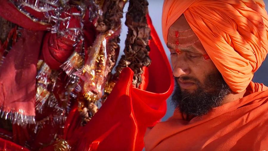 Hindu priest standing near religious offerings