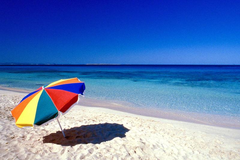 Multi colored umbrella on beach against clear blue sky