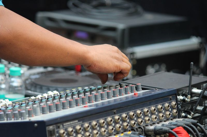 Cropped hand of man mixing sound at studio