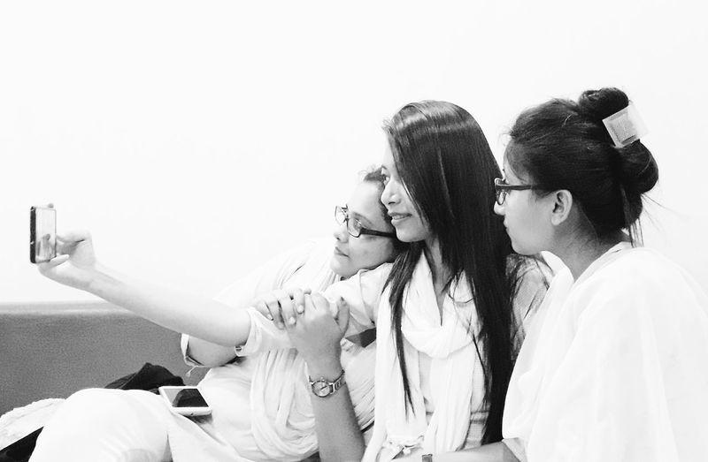 Female friends taking selfie against white background