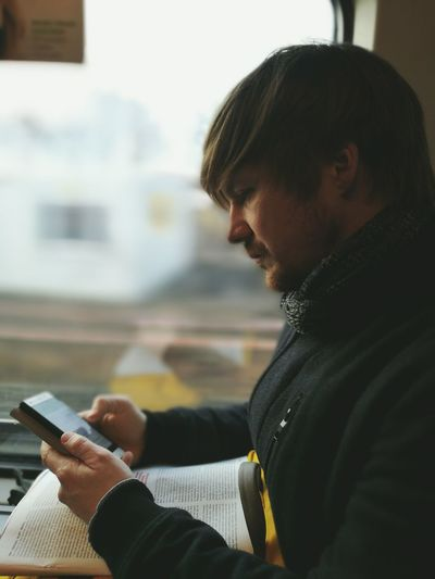 Side View Of Man Using Mobile Phone While Sitting Against Window In Train