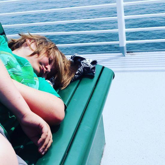Boy sleeping on bench in boat