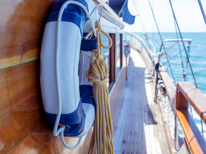Close-up of life belt and rope hanging on boat