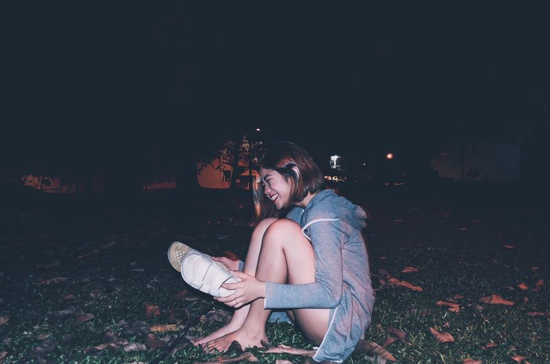 Portrait of young woman sitting on field at night