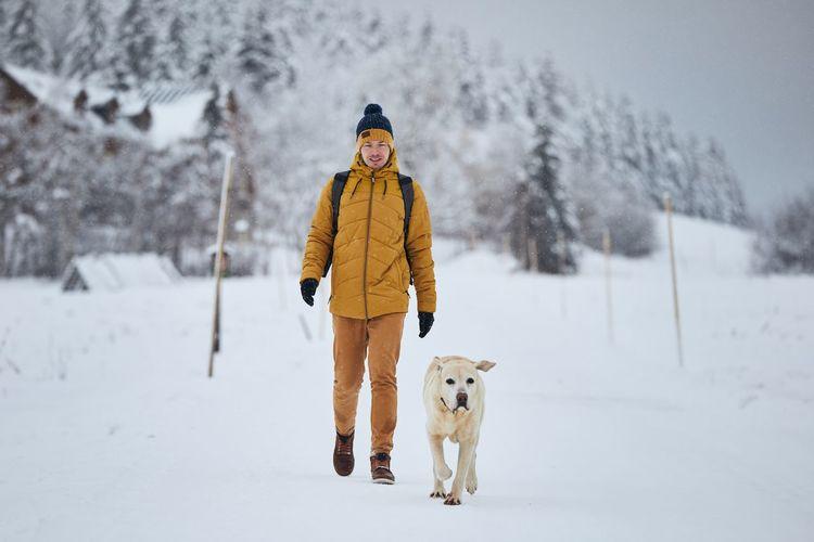 Man and dog walking on snow