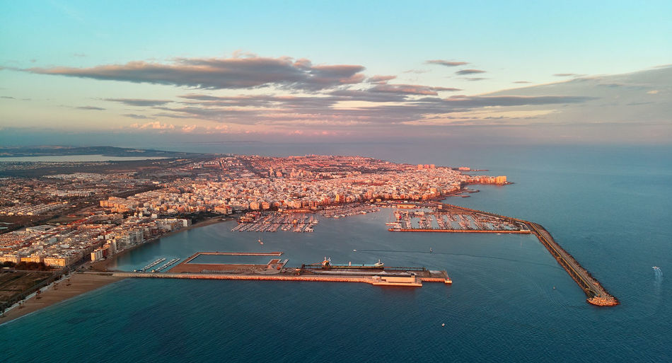 High angle view of city by sea against sky during sunset