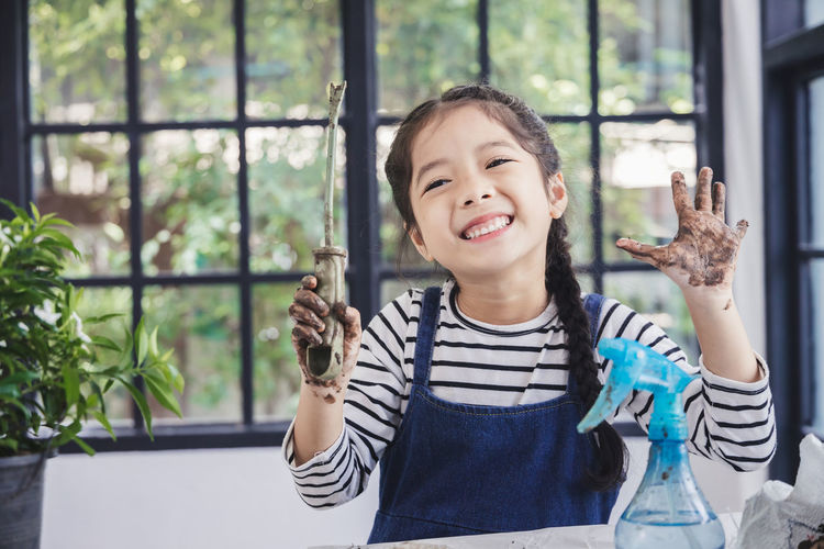 Portrait of smiling girl holding window