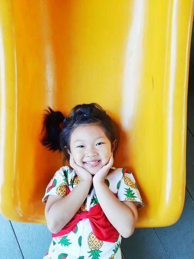 High angle portrait of cute girl touching cheek on slide