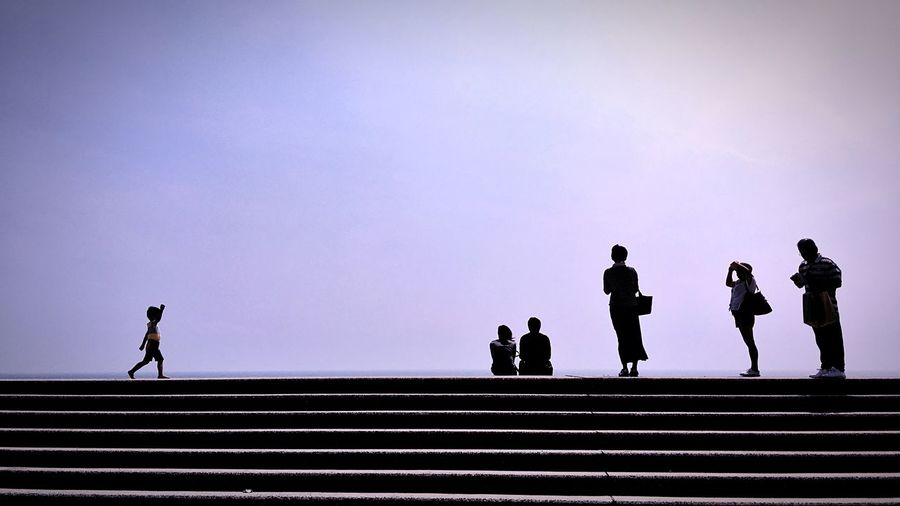 Silhouette people on steps against clear sky