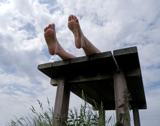 Low section of man relaxing on wood against sky