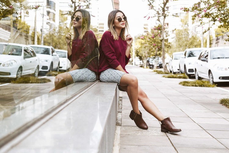 Young Woman Sitting On Sidewalk By Reflection Glass Building