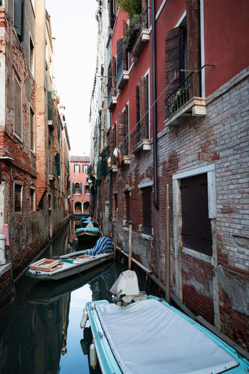 Boats amidst buildings on canal in city