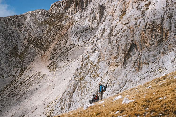 People walking on rock by mountain