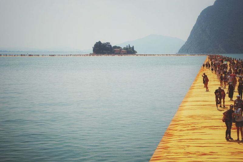 Walking on the Floating piers | People Walking Sunshine Feel The Journey Edge Of Imagination The Floating Piers Nature Lake Still Life The Essence Of Summer Original Experiences Getting Inspired Christo And The Floating Piers Fine Art Close-up Tailored To You Point Of View Golden Moments  Showcase July 43 Golden Moments Umbrellas Lago D'Iseo EyeEm Italy |
