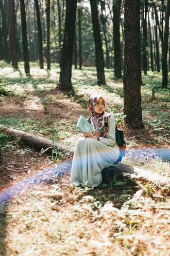 Young woman sitting on tree trunk in forest