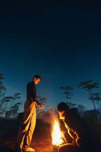 People by campfire against sky at night