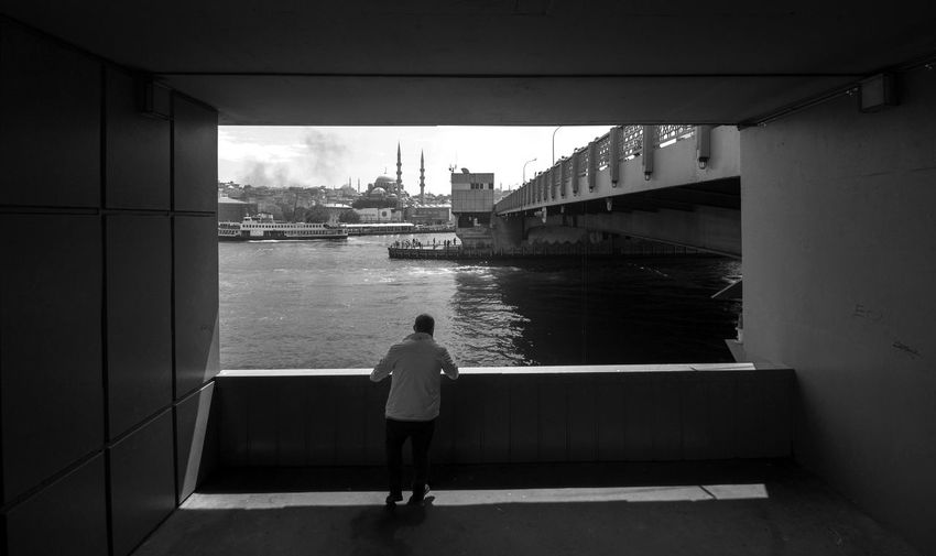 Rear view of woman looking at view of bridge over river
