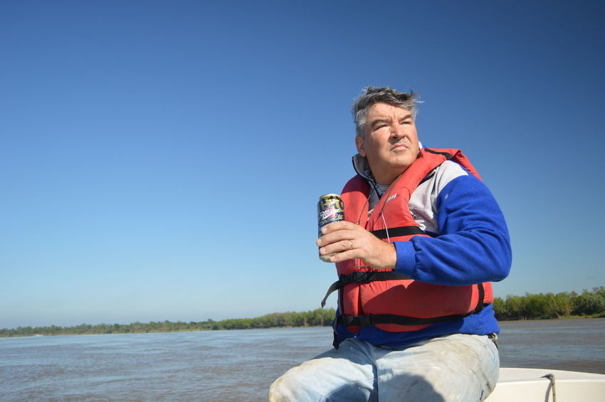 A refreshing drink after a good day of fishing - Ruso One Person Holding Drink Water Nature Three Quarter Length Smiling Leisure Activity Day Sky Blue Adult Drinking Sitting Clear Sky Lifestyles Refreshment Happiness Outdoors Fisherman River