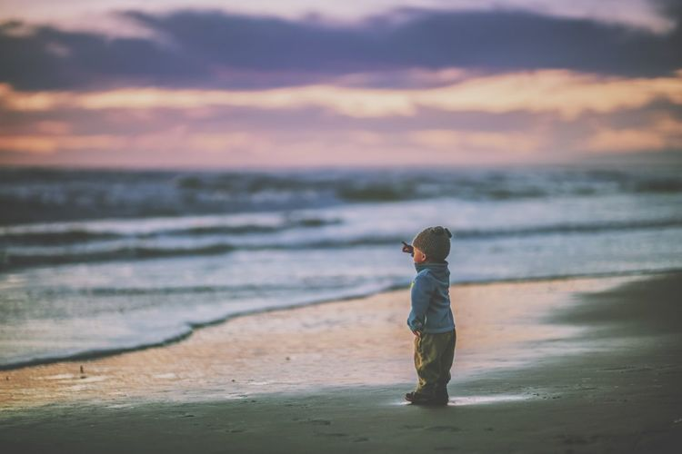 Side view of boy standing on calm beach