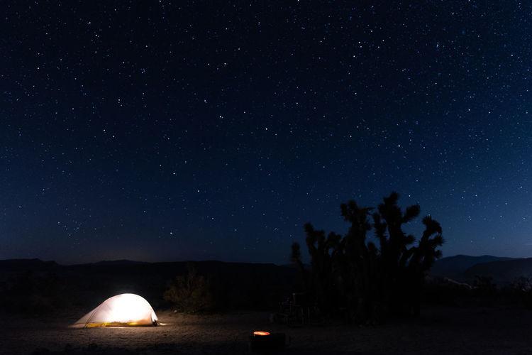 Illuminated tent on land against star field at night