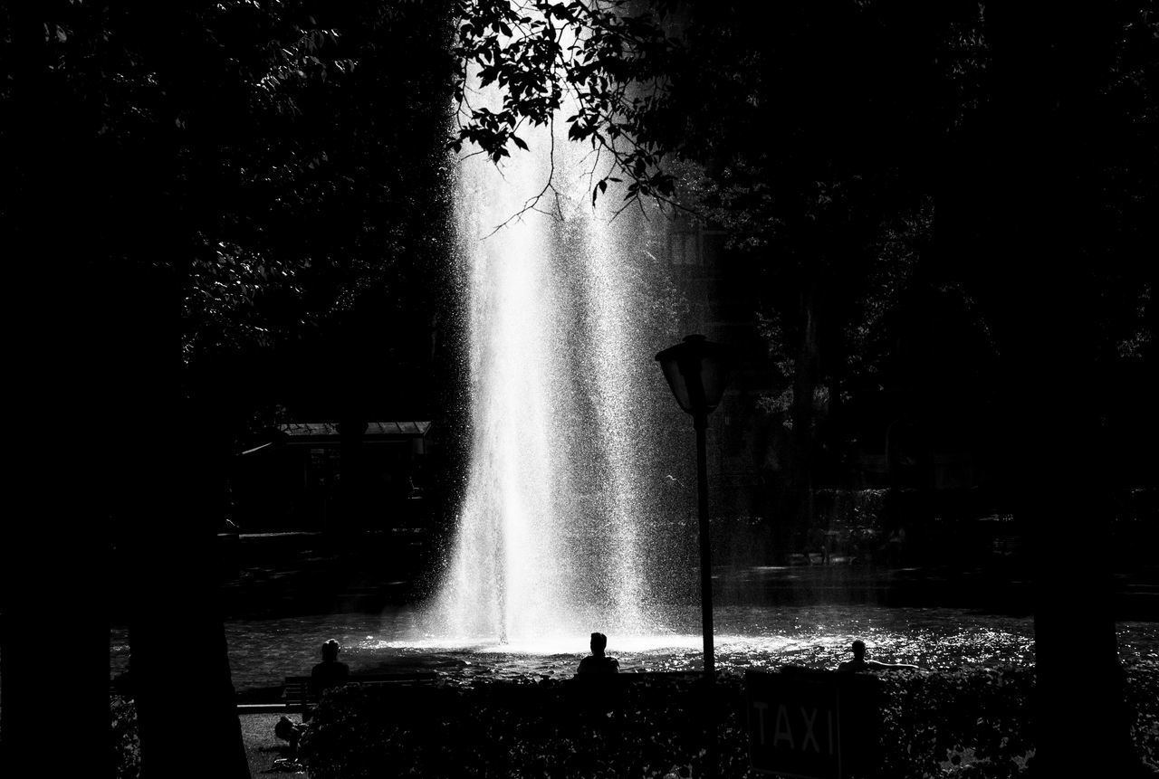 fountain, motion, water, long exposure, tree, spraying, flowing water, outdoors, nature, splashing, waterfall, silhouette, day, beauty in nature, drinking fountain, no people, scenics, forest, sky