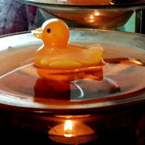 A Bright Yellow Wax Melt Duck Floating in Melted Wax . Featuring Candle No People Close-up Flame Indoors  Day Relaxing Reflections Background Candle Holder Mirrored Flame Oil Burner Beautiful Reflecting Wax Melt Melting