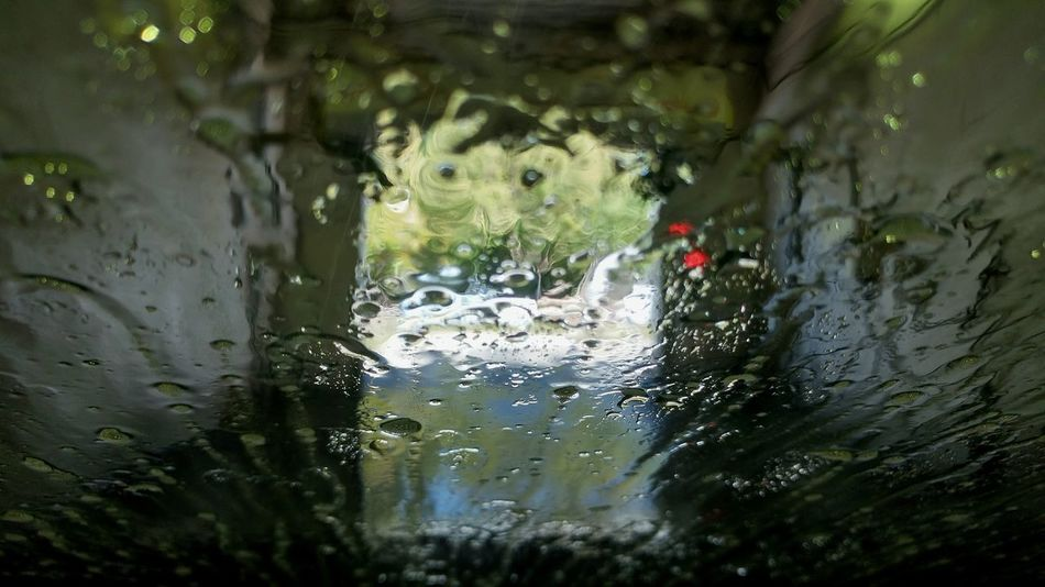 water distorts the light through the windshield view of a driver's path. No People Distorted View Obscured View Water Bending Light Foggy Vision Muddy Vision Car Wash Land Vehicle Car Wet Reflection Window Close-up Window Washer Droplet