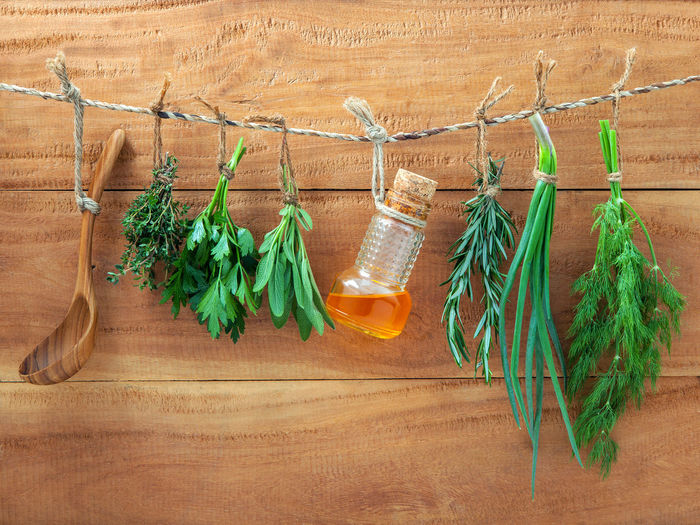 Herbs hanging on rope against wooden wall
