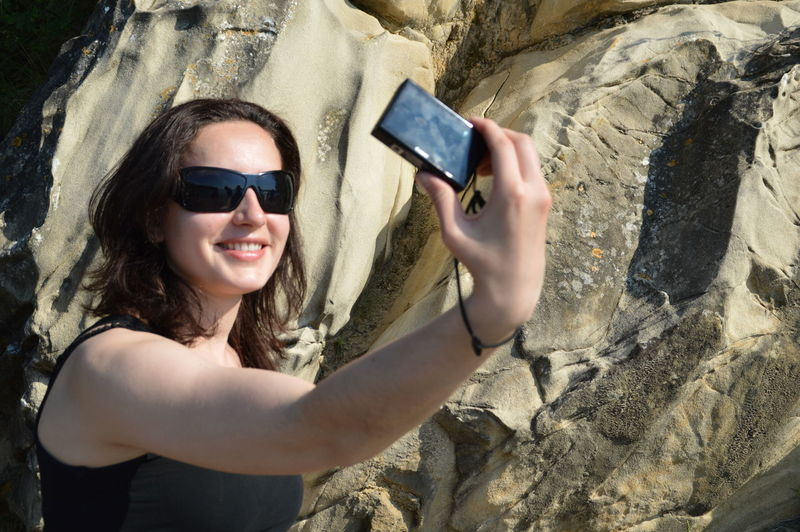 Happy Woman Taking Selfie From Camera Against Rock Formation