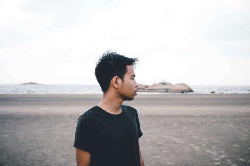Young man standing at beach against sky