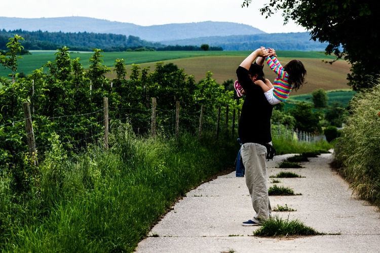 Side View Of Father Carrying Daughter On Shoulder Amidst Plants