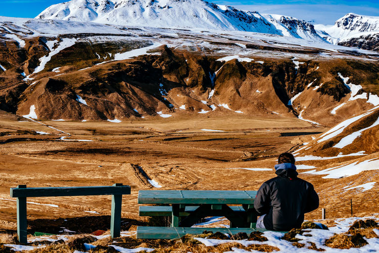Scenic view of person sitting on bench