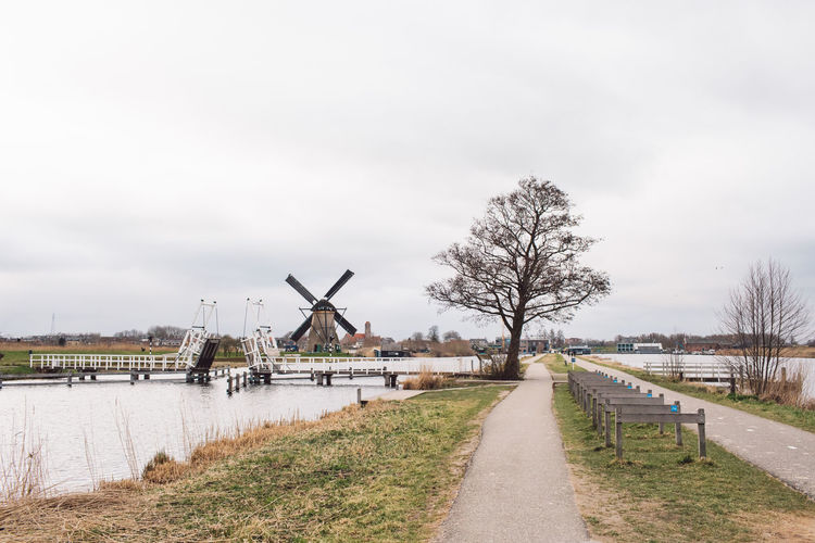 Traditional windmill by canal against sky