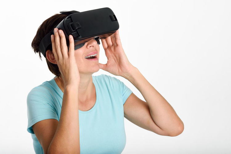 Mature woman using virtual reality against white background