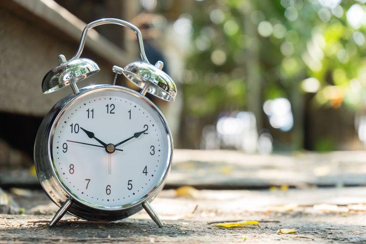 Close-up of alarm clock on footpath