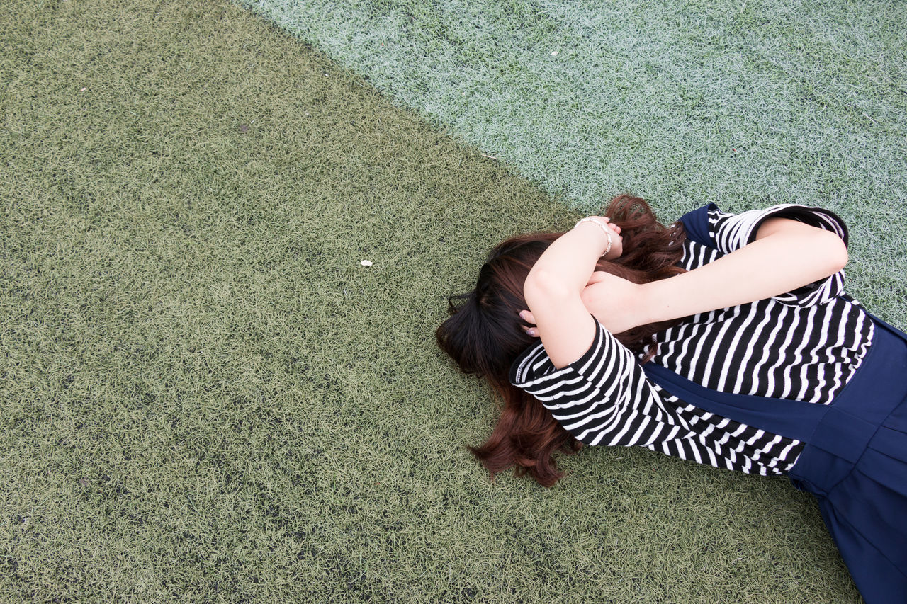 High Angle View Of Woman Covering Face With Hands While Lying On Grassy Field