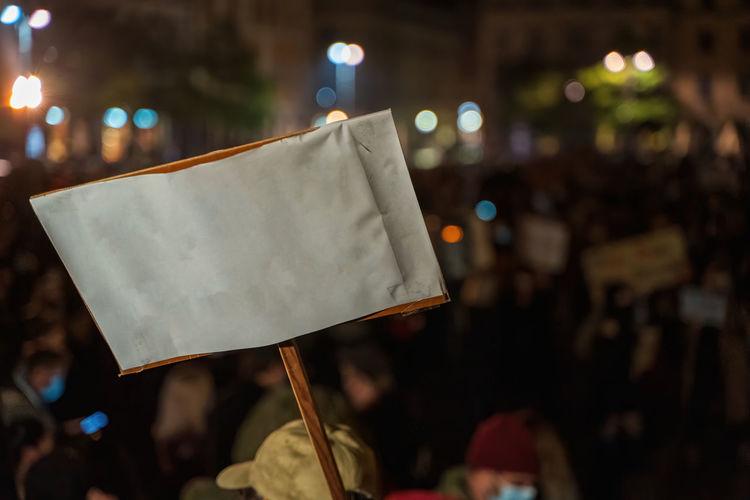 Close-up of person holding umbrella against illuminated street at night