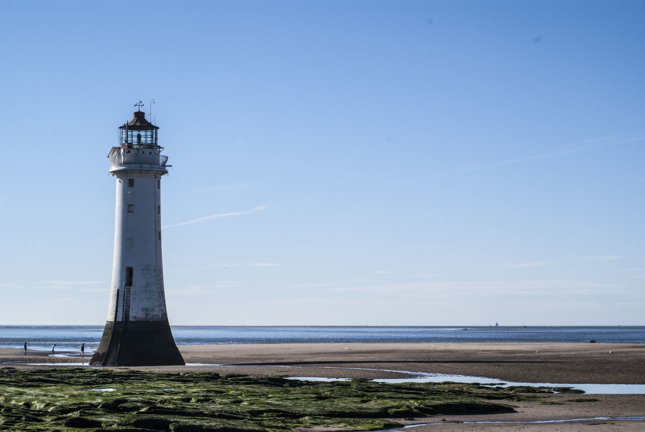 lighthouse, guidance, sea, direction, horizon over water, safety, tranquil scene, day, protection, architecture, beach, scenics, nature, sky, water, tranquility, beauty in nature, outdoors, no people, built structure, blue, travel destinations, building exterior
