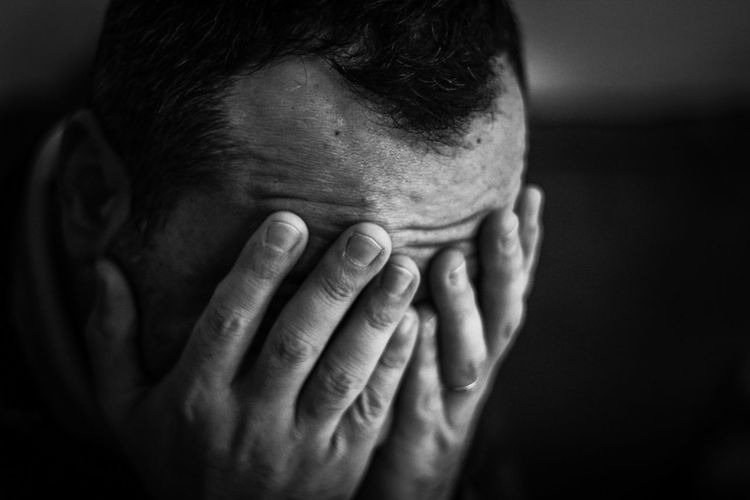 Close-up sad man covering face with hands