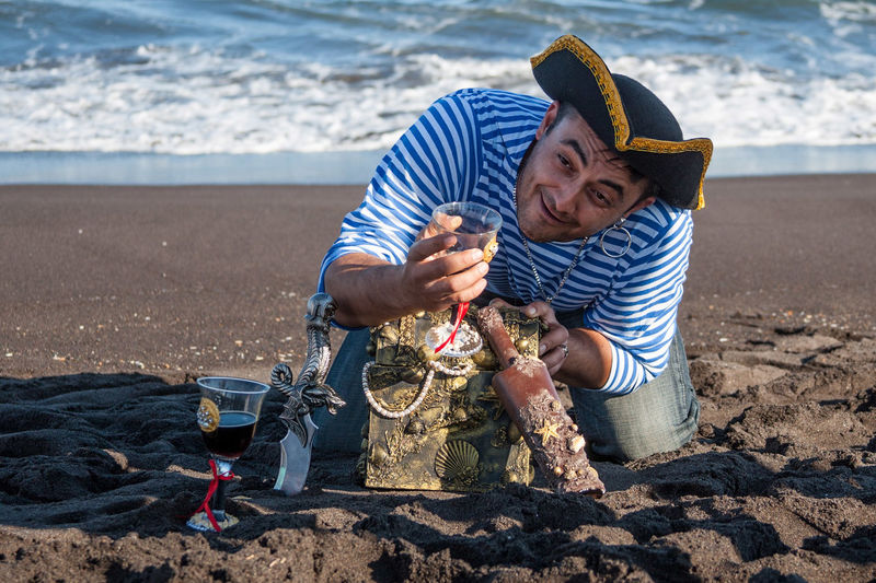 Pirate Holding Wineglass With Treasure Chest At Beach