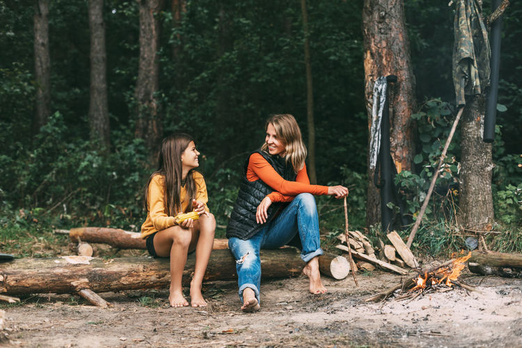 Friends sitting on wood in forest