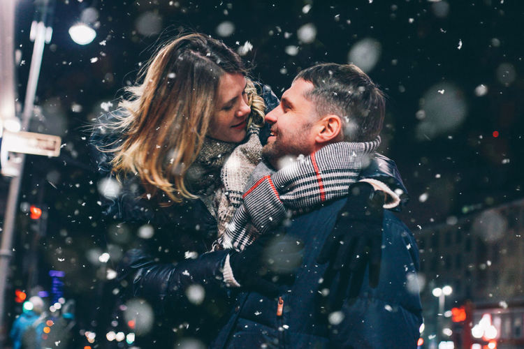 Real young couple walking together in night city under snow, kissing and smiling, winter romance, lifestyle Winter Two People Positive Emotion Night Clothing Cold Temperature Men Love Togetherness Emotion Young Adult Snowing Warm Clothing Women Young Women Snow Happiness Adult Couple - Relationship
