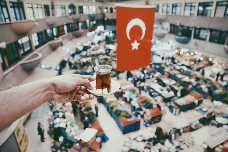 Cropped hand holding glass of tea against turkish flag